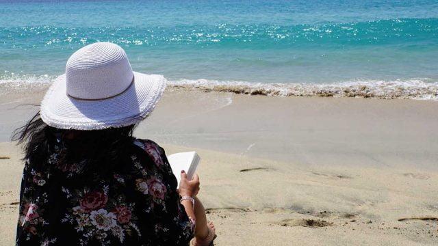 Plaža, more, žena, čitanje knjige